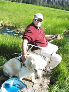 Hal Long with his faithful guide dog, Floyd, on a fishing adventure.