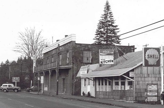 Intersection Boones Ferry and Tualatin Rd. Brick store, old Post Office, Mae's Cafe, Bonk's Shell. c. 1975.